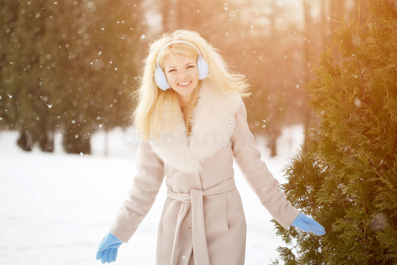 Winter woman on background of winter landscape? sun. Fashion girl in forest wonderland. Winter sunset scene. Model in sunlight, b. Acklight royalty free stock image