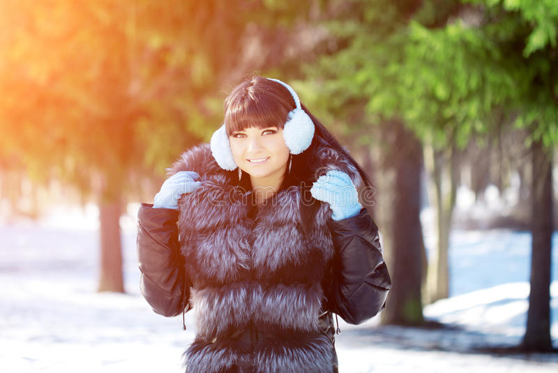 Winter woman on background of winter landscape? sun. Fashion girl in forest wonderland. Winter sunset scene. Model in sunlight, b. Acklight royalty free stock images