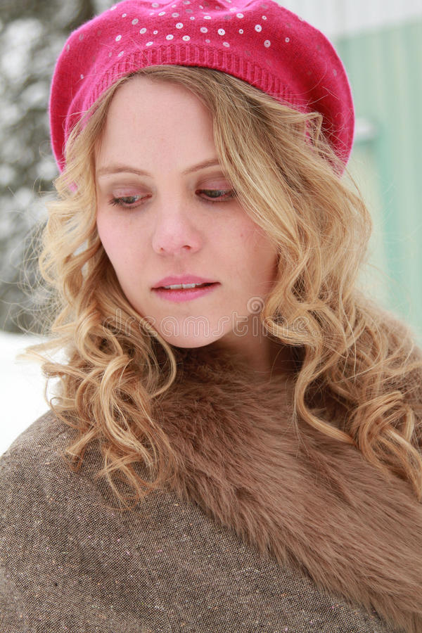 Winter Woman Portrait Looking Down. Portrait of a slightly smiling, wholesome, beautiful, green eyed young woman wearing a fur jacket and pink beret in snow and royalty free stock image