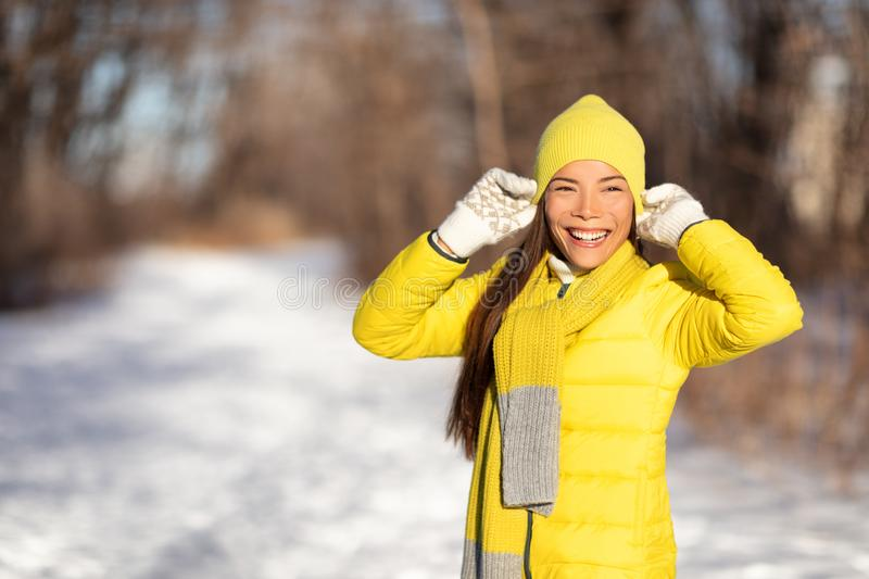 Winter woman smiling emotion outside in nature forest Asian girl happy wearing yellow hat and gloves for cold season. Walk in stock images