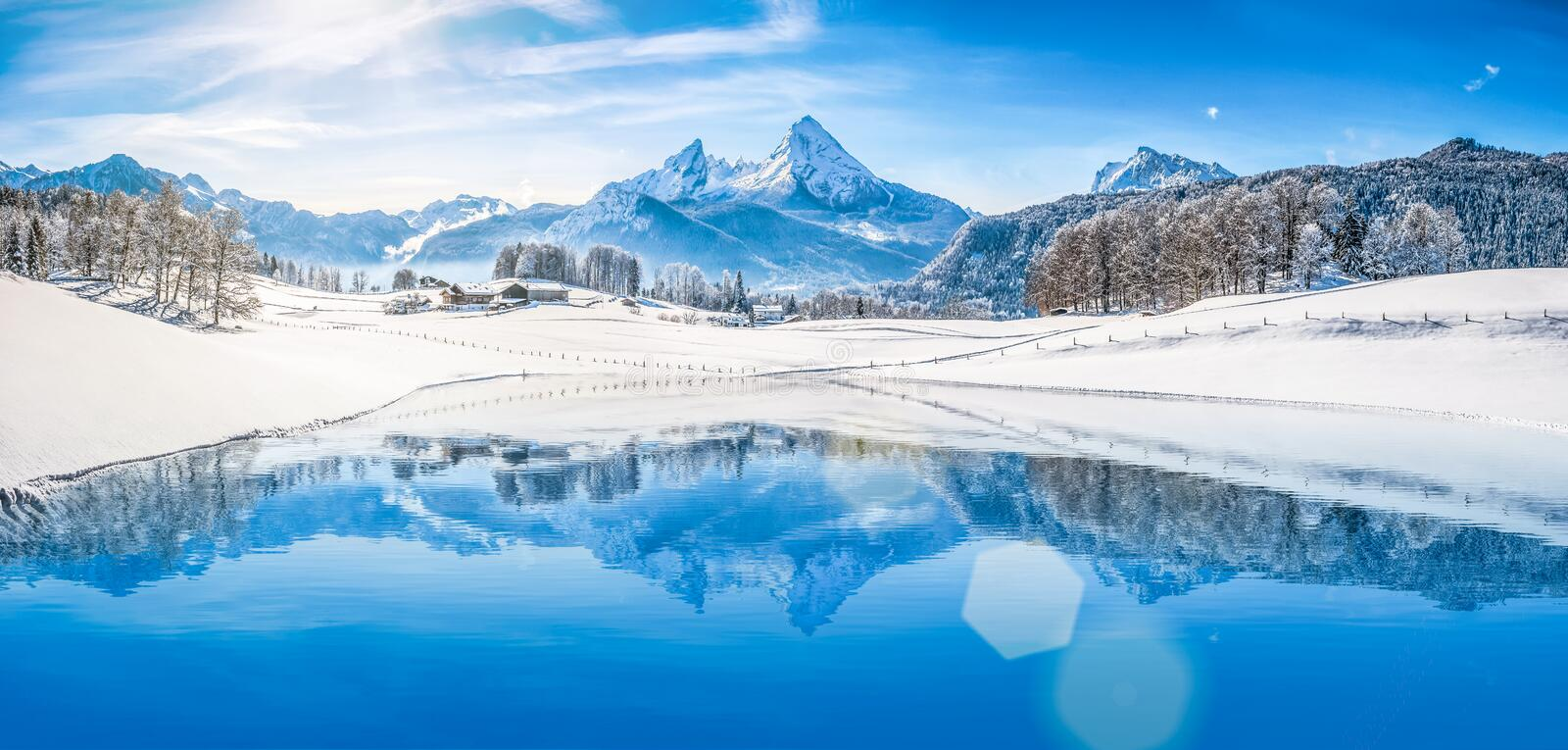 Winter wonderland in the Alps reflecting in crystal clear mountain lake. Panoramic view of beautiful white winter wonderland scenery in the Alps with snowy royalty free stock photos