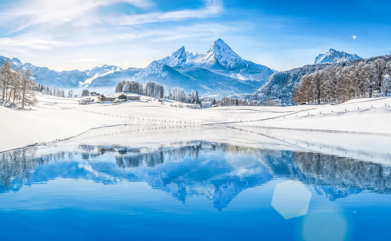 Winter wonderland in the Alps reflecting in crystal clear mountain lake. Panoramic view of beautiful white winter wonderland scenery in the Alps with snowy stock photos