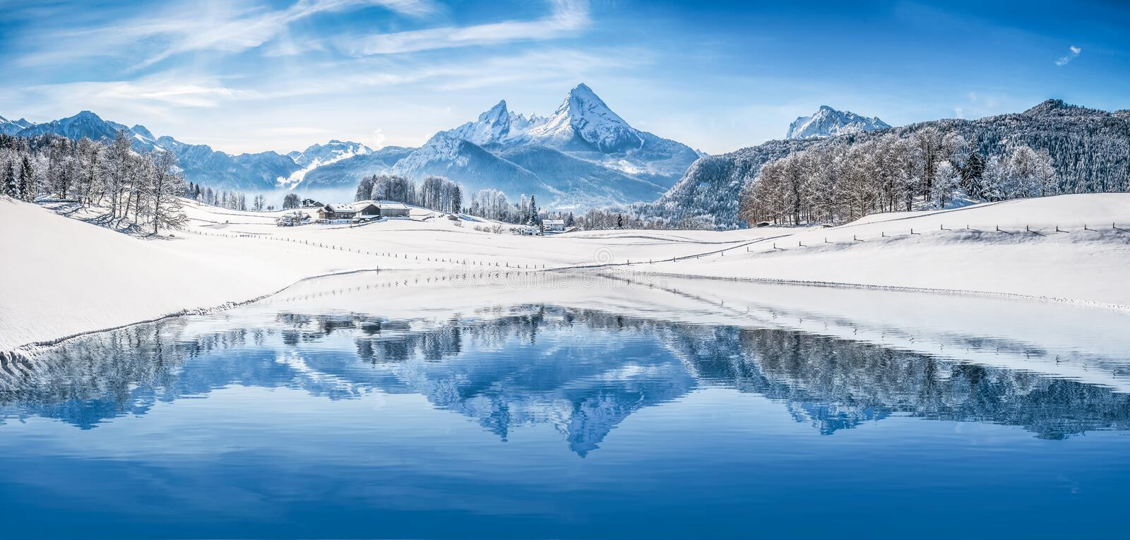 Winter wonderland in the Alps reflecting in crystal clear mountain lake. Panoramic view of beautiful white winter wonderland scenery in the Alps with snowy stock photography