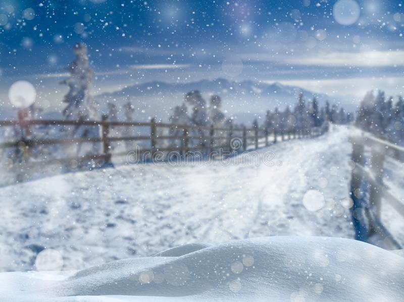 Winter wonderland landscape. Snow with bokeh soft lights falling over a Christmas scenic blurred background.  royalty free stock images