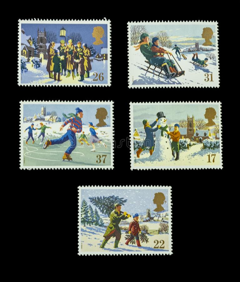 Winter wonderland stamps. Painted pictures of winter scenes on British postage stamps set on a black background royalty free stock photos