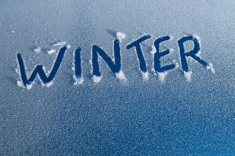 Winter Word in Car Frost. The word WINTER written in frost on a blue car royalty free stock image