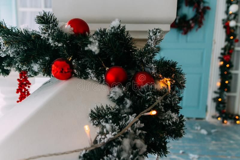 Winter wreath hanging on a door of house decorated by Christmas pine branch with red baubles and decorative snow. royalty free stock photography