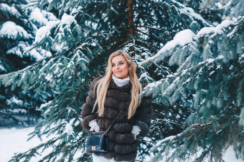 Winter young woman portrait. Beauty Joyful Model Girl laughing and having fun in winter forest. Beautiful young woman royalty free stock image