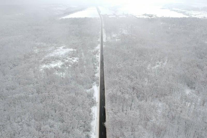 Winteransicht einer Straße mitten in dem Wald stockbilder
