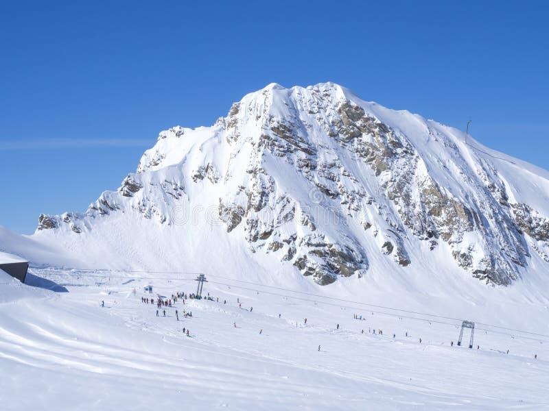 Winterberge gestalten mit bunten gekleideten Skifahrern auf weißen Schneesteigungen landschaftlich Ansicht von der Spitze Kitzste lizenzfreie stockfotografie
