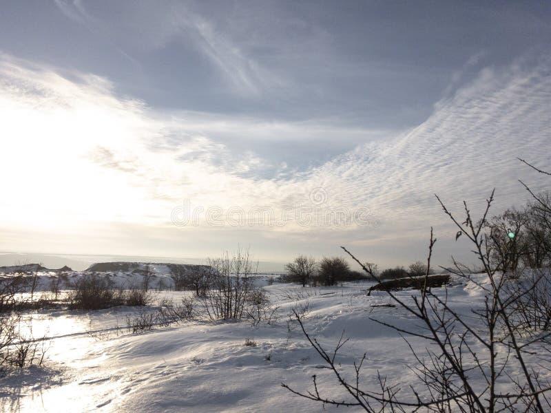 Winterberglandschaft mit schneebedeckten Bäumen und Wolken stockbild