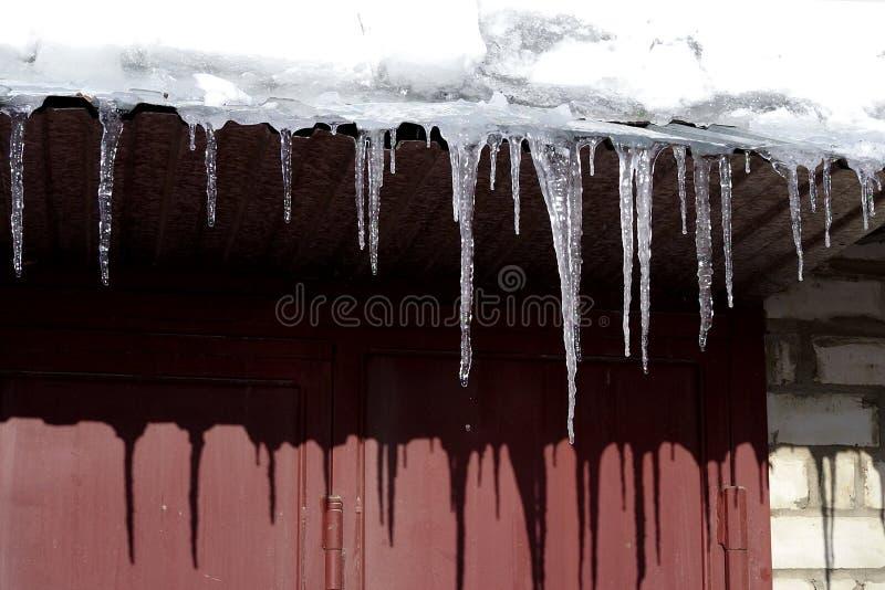 Wintereiszapfen, die von den Dachgesimsen des Dachs hängen lizenzfreie stockbilder
