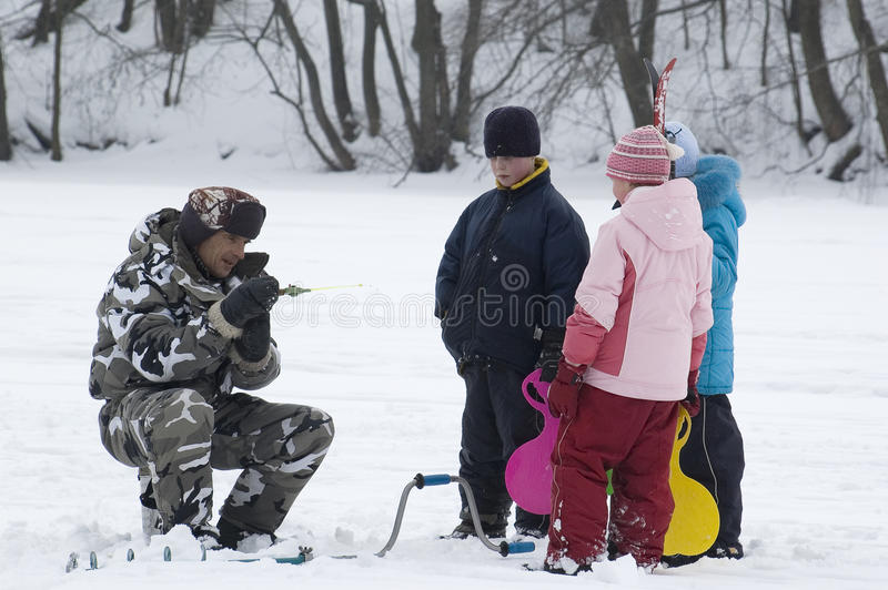 Winterfischen. Alter Fischer und junge Zuschauer lizenzfreies stockbild