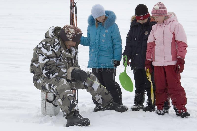 Winterfischen. Alter Fischer und junge Zuschauer lizenzfreie stockfotografie