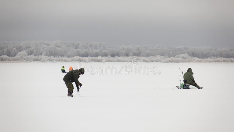 Winterfischerei auf Eis, natürlicher Hintergrund Fischer am See stockfotografie