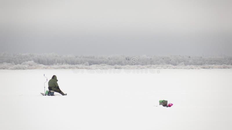 Winterfischerei auf Eis, natürlicher Hintergrund Fischer am See lizenzfreies stockbild
