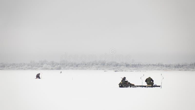 Winterfischerei auf Eis, natürlicher Hintergrund Fischer am See lizenzfreie stockbilder