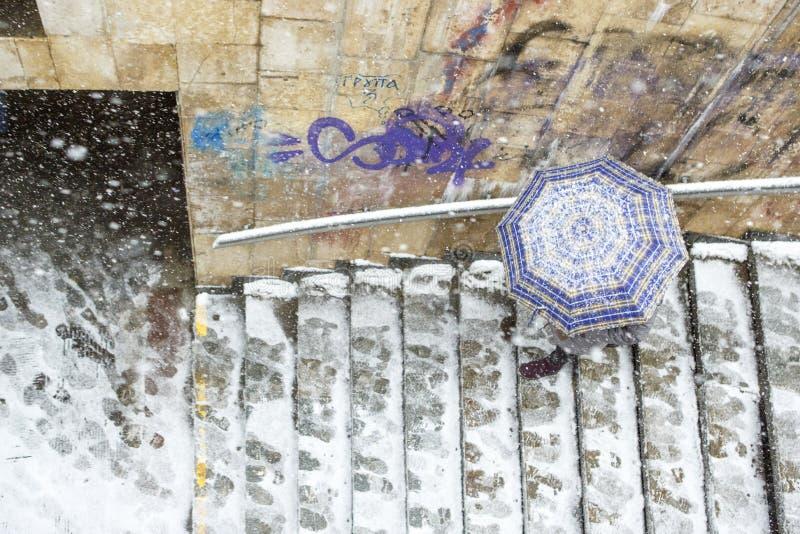 Winterfrau unter einem Regenschirm auf einem Stadthintergrund lizenzfreie stockbilder