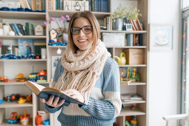 Winterherbstporträt von jungen schönen tragenden Gläsern der Studentin in gestricktem warmem Schal- und Strickjackenlesebuch zuha lizenzfreie stockfotos