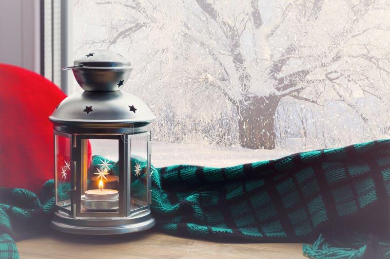 Winterhintergrundlaterne mit Kerze und Plaid mit Kissen auf Fensterbrett und Winterszene draußen stockbilder