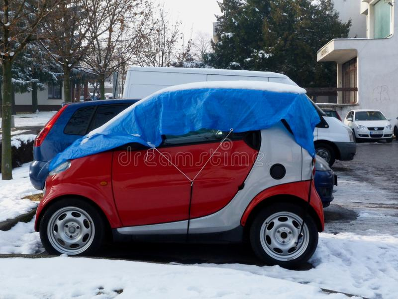 Make shift winterized small red car in public parking lot. Winterized small red car in make shift manner in public parking lot with wintry scene, snow and pine stock photo