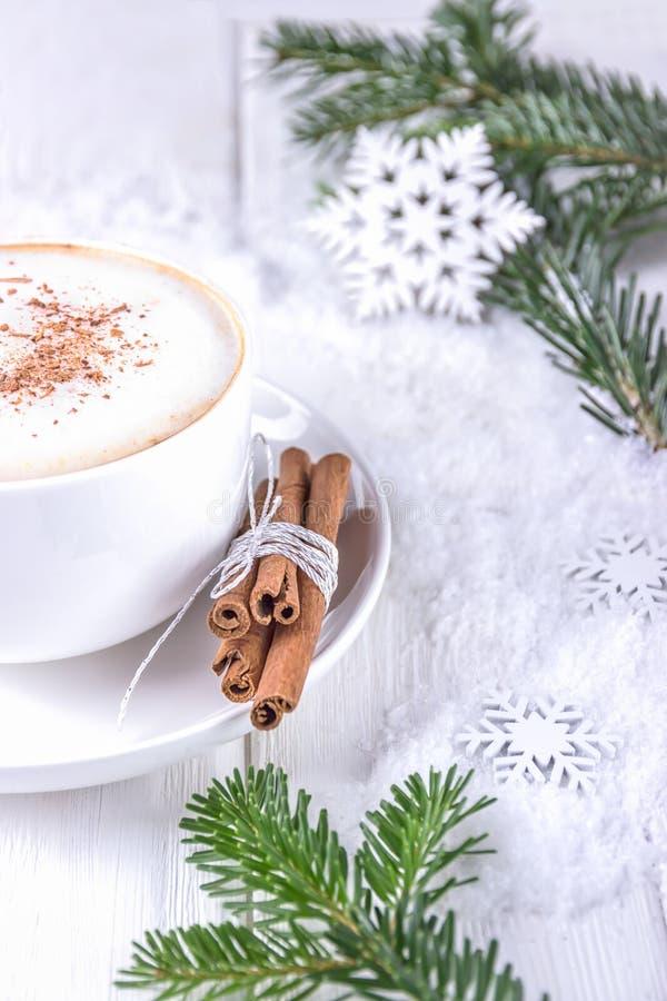 Winterkaffeecappuccino- und -weihnachtsbaumaste Weiße Schale Cappuccino mit Zimt auf einem hölzernen Hintergrund stockbild
