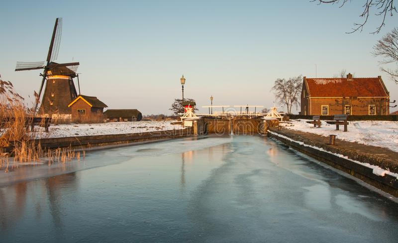 Winterlandscape néerlandais avec le moulin à vent et l'écluse photos stock