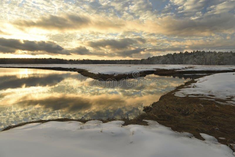 Winterlandschaft des Flusses bei Sonnenuntergang und des Waldes im Abstand auf dem Horizont lizenzfreie stockfotos