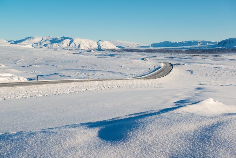 Winterlandschaft, die leere Straße, die durch Schnee umgeben wurde, bedeckte Berge, Island mit einer Kappe lizenzfreie stockfotografie