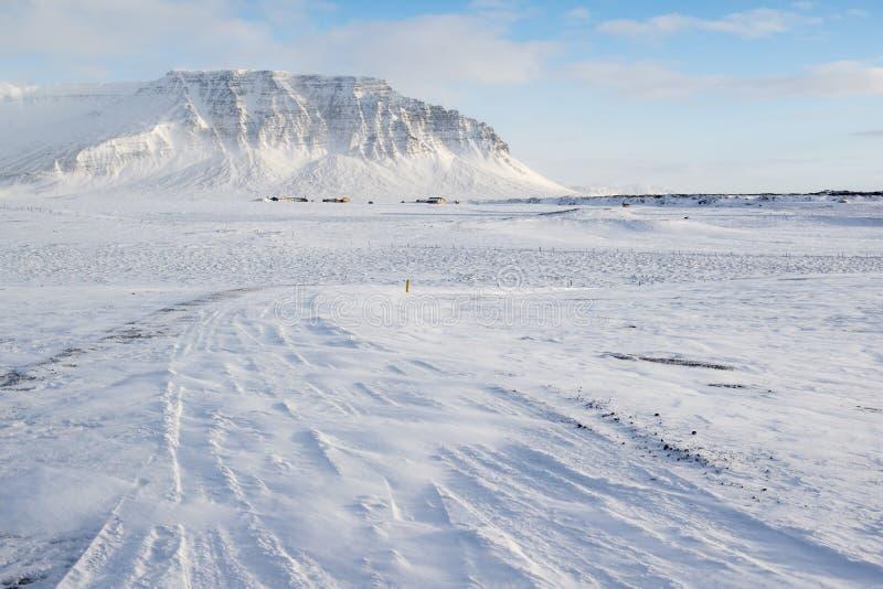 Winterlandschaft mit Berg, vielem Schnee und kleinen Gutshäusern, Island lizenzfreies stockbild