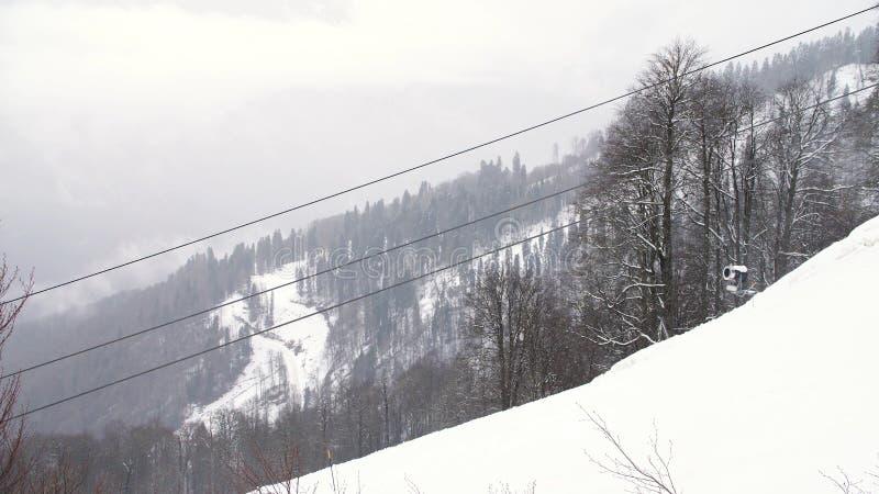 Winterlandschaft mit dem Berghang umfasst durch schneebedeckte Bäume und das funikuläre mit beweglichen Kabinen, Skiort Kunst ski stockfoto