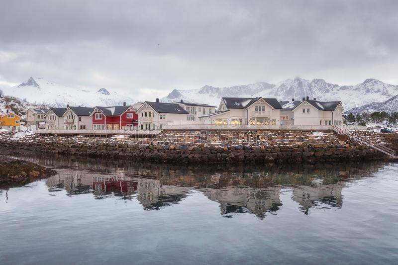 Winterlandschaft mit den weißen und roten Häusern, Reflexion im Wasser und schneebedeckte Bergspitzen, Kabelvag, Lofoten-Inseln,  lizenzfreie stockfotos