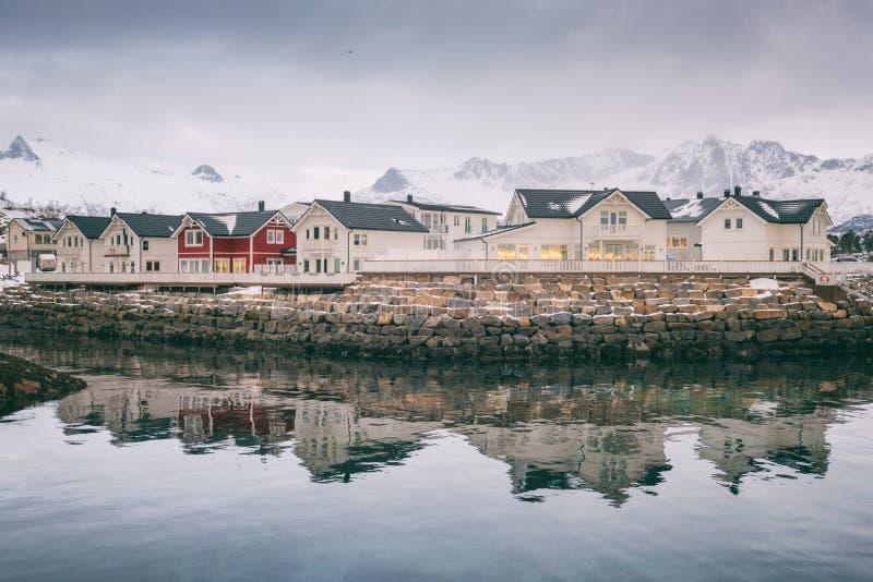 Winterlandschaft mit den weißen und roten Häusern, Reflexion im Wasser und schneebedeckte Bergspitzen, Kabelvag, Lofoten-Inseln,  lizenzfreies stockbild