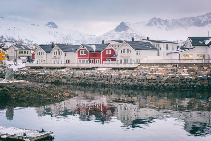 Winterlandschaft mit den weißen und roten Häusern, Reflexion im Wasser und schneebedeckte Bergspitzen, Kabelvag, Lofoten-Inseln,  stockbild