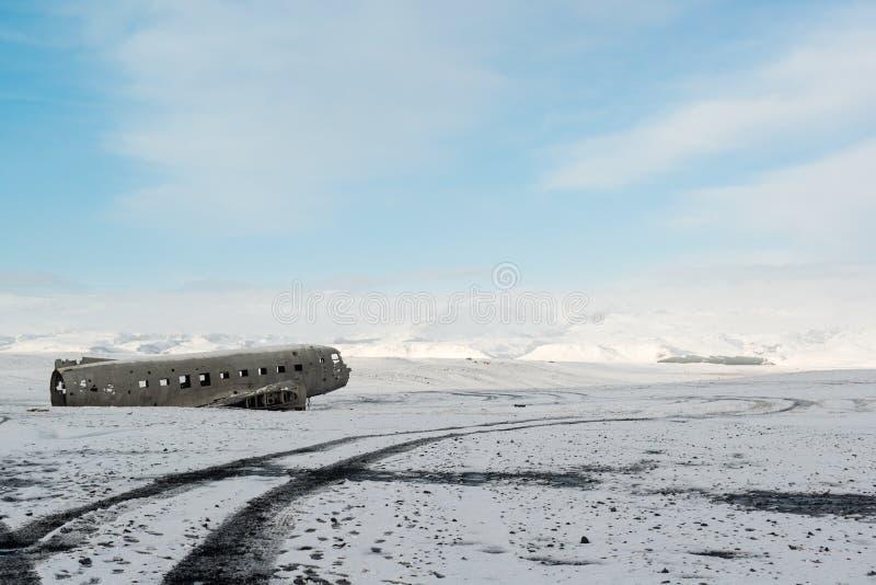 Winterlandschaft mit Flugzeugschiffbruch und -schnee bedeckte Berge, Island mit einer Kappe stockfoto