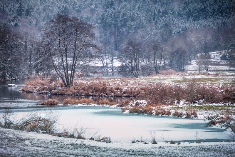 Winterlandschaft mit Fluss regen im Bayern Deutschland lizenzfreie stockbilder