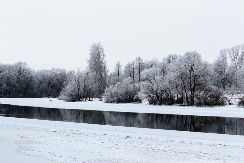 Winterlandschaft mit Fluss und Schnee lizenzfreie stockbilder