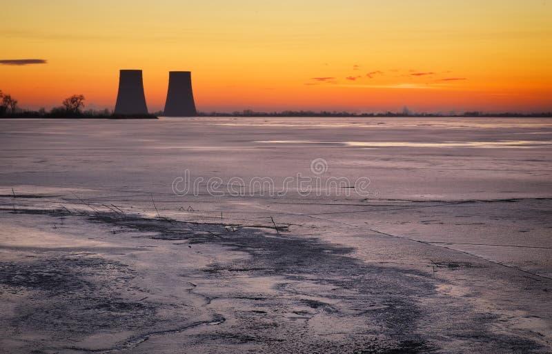 Winterlandschaft mit gefrorenem See und Kraftwerk stockfotos