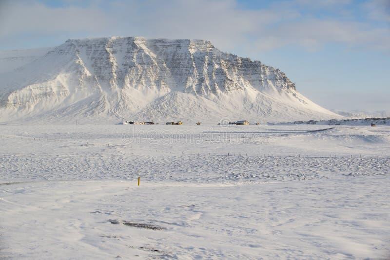 Winterlandschaft mit Schnee bedeckte Berg, viel Schnee und kleine Gutshäuser, Island mit einer Kappe lizenzfreie stockbilder