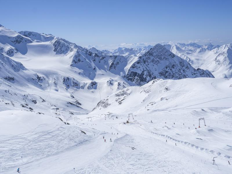 Winterlandschaft mit Schnee bedeckte Berghänge und Pistes mit den Skifahrern, die sonnigen Tag des Frühlinges am Skiort Stubai ge lizenzfreie stockfotografie