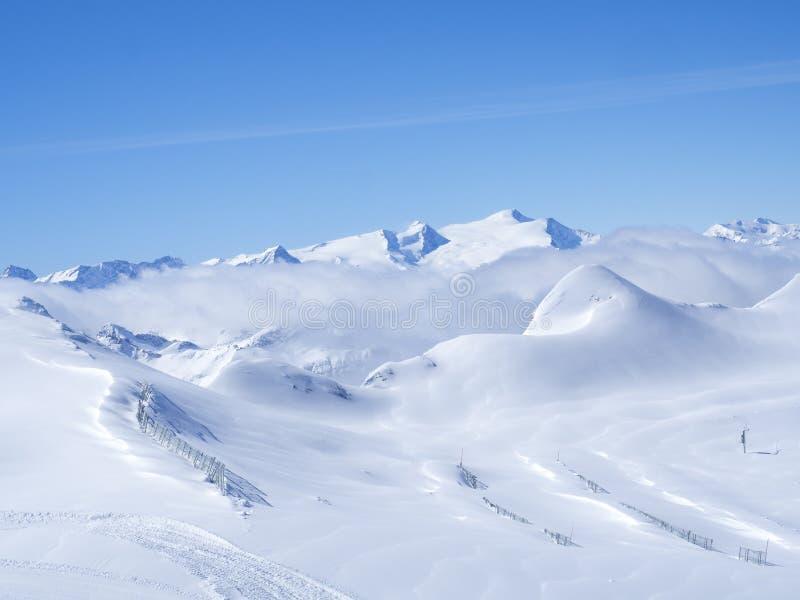 Winterlandschaft mit Schnee bedeckte Steigungen und blauen Himmel, Ansicht von der Spitze Kitzsteinhorn-Berges an Kaprun-Ski stockbild
