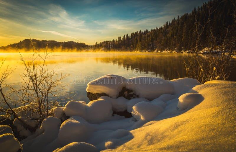 Winterlandschaft mit Schnee und warmem Sonnenunterganglicht lizenzfreie stockfotos