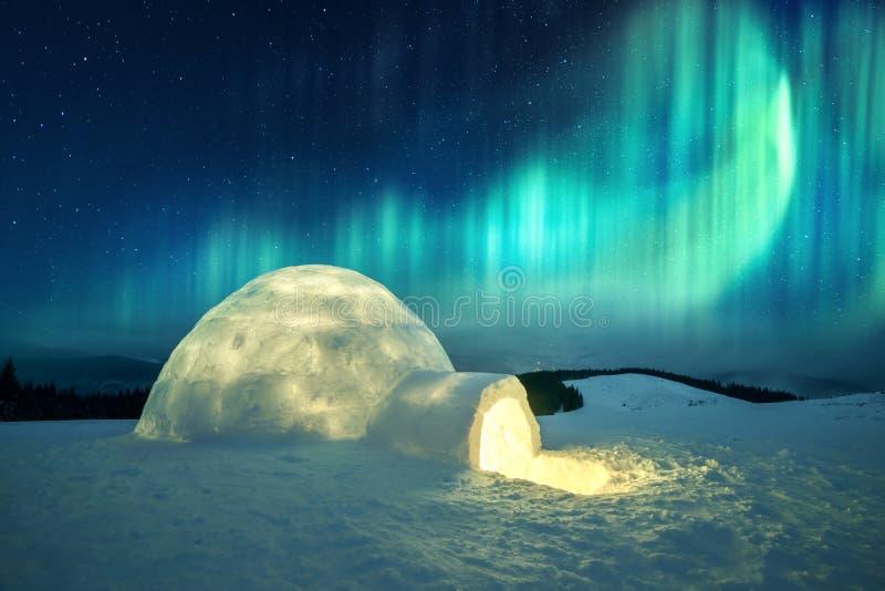 Winterliche Szene mit glühenden Polarlichtern und schneebedecktem Iglu lizenzfreie stockbilder