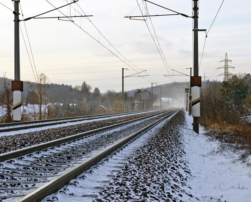 Winterly snowy railway line. With electrical overhead wiring stock image