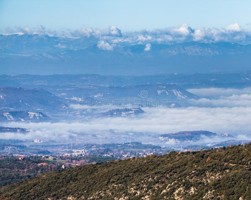The Pyrenees mountains over valley cloudscape. Winterly view from the Pla de la Calma highlands in northeastern Catalonia of the chain of the Pyrenees mountains royalty free stock photography