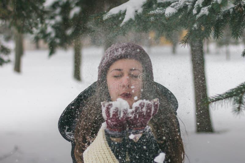 Wintermädchen mit einem Schlagschnee des roten Hutes stockfoto