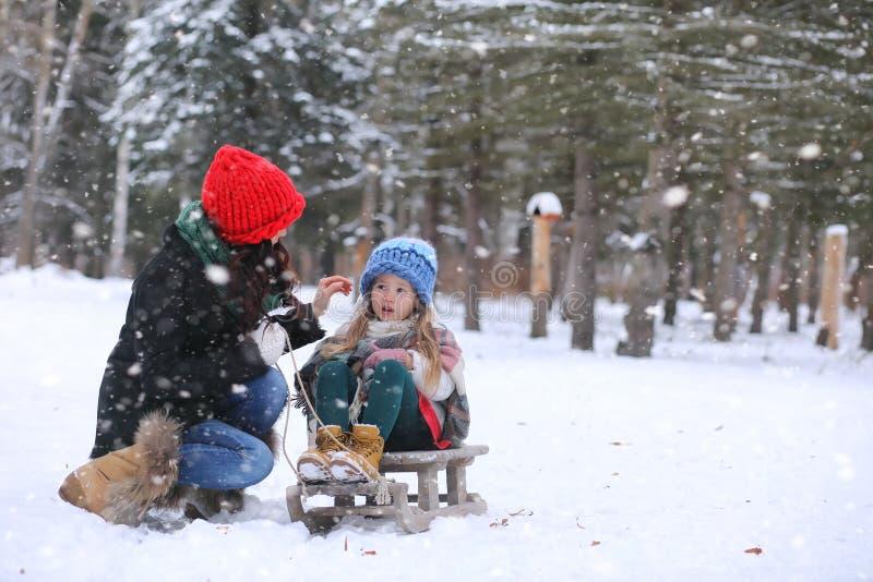Wintermärchen, eine junge Mutter und ihre Tochter reiten einen Schlitten stockbild