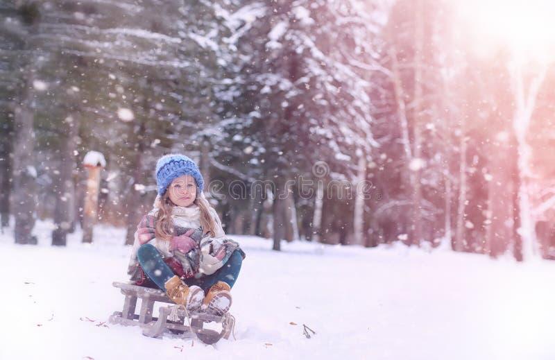Wintermärchen, eine junge Mutter und ihre Tochter reiten einen Schlitten stockbilder