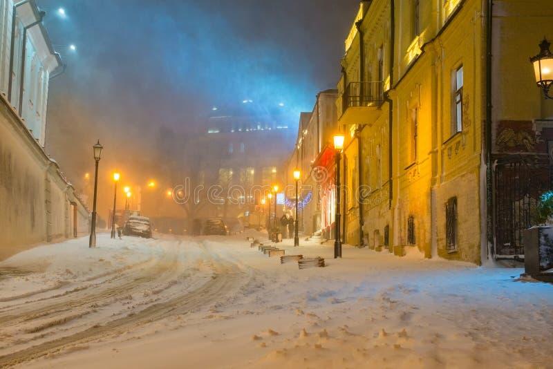Winternachtlandschaft, glättend in der Nachtschneebedeckten Straße unter Schneefällen lizenzfreie stockbilder