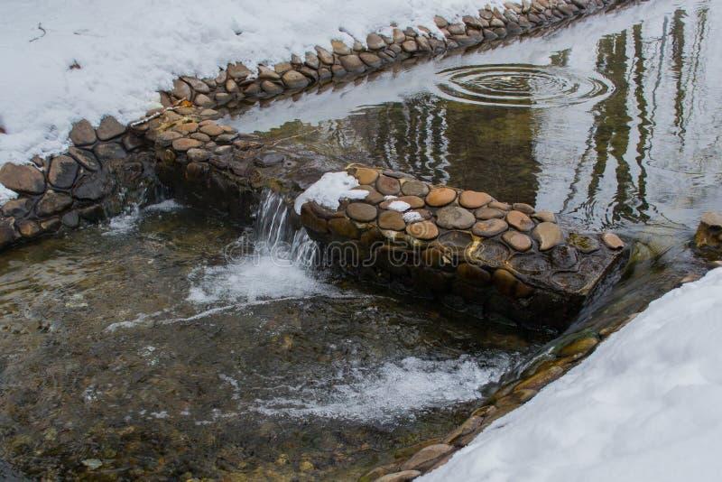 Winternebenfluß mit einem Wasserfall und einer Reflexion von Bäumen stockbilder